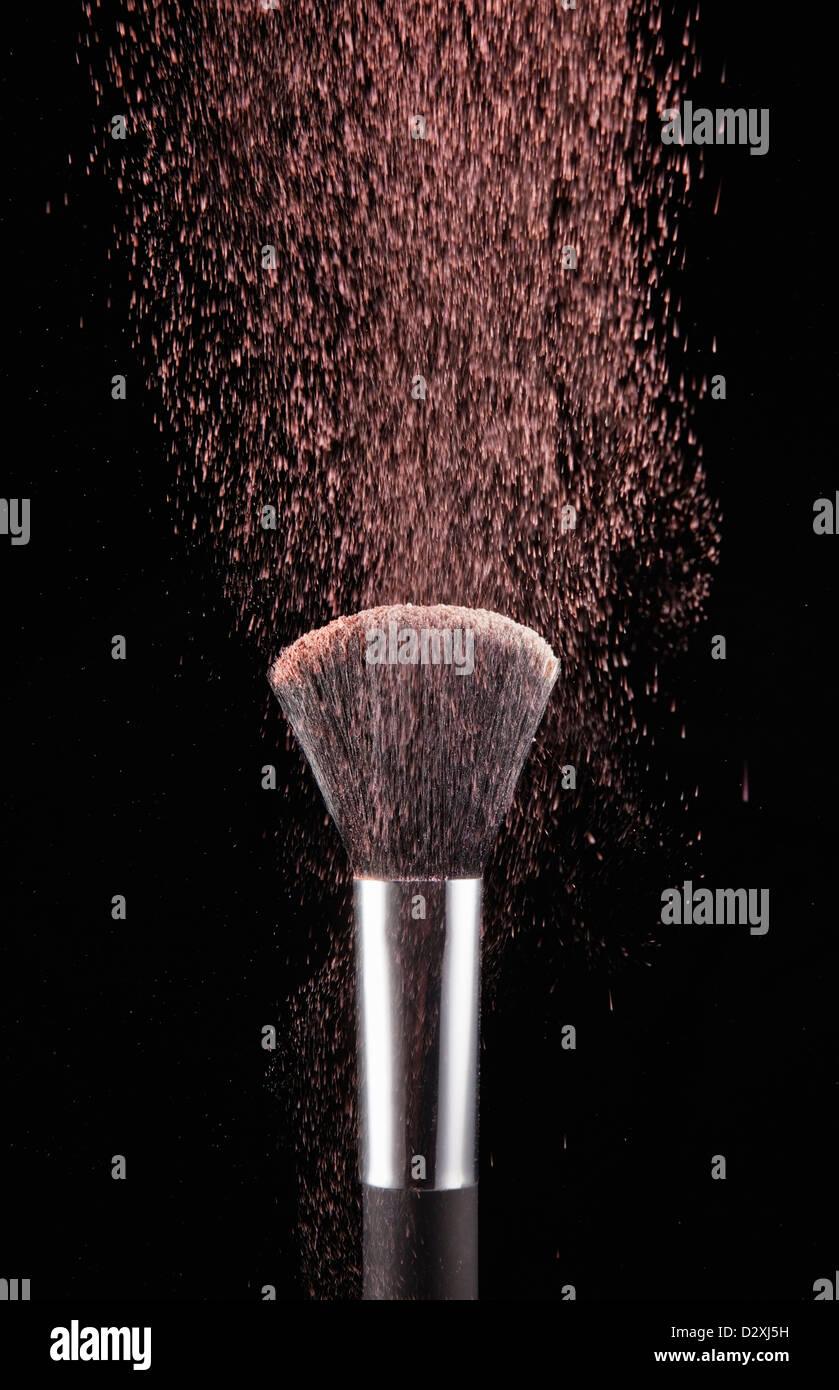 Erröten Sie Pulver weht aus Make-up Pinsel Stockbild