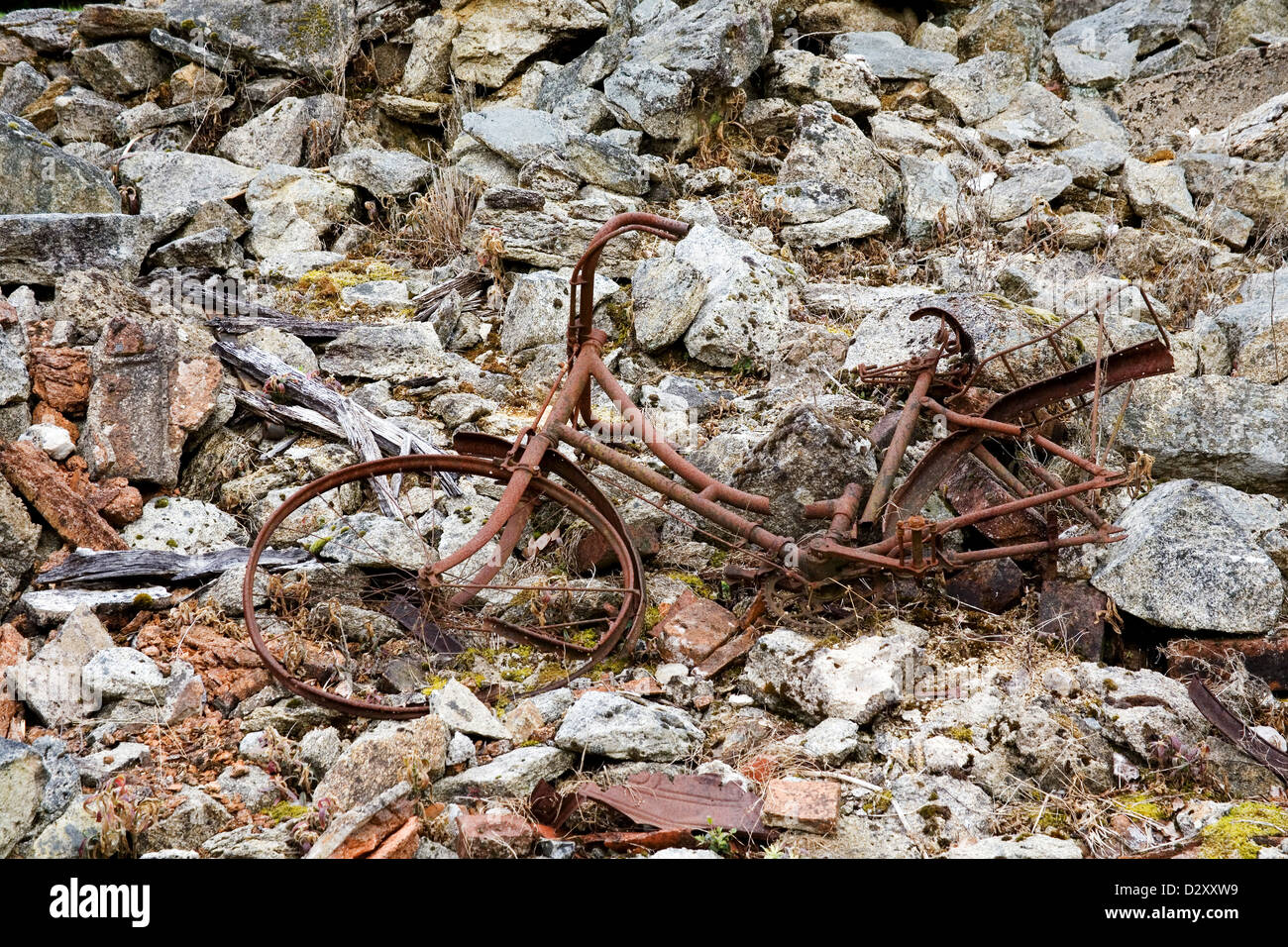 Eine rostige alte Fahrrad Orange in Farbe liegt auf den Trümmern ...