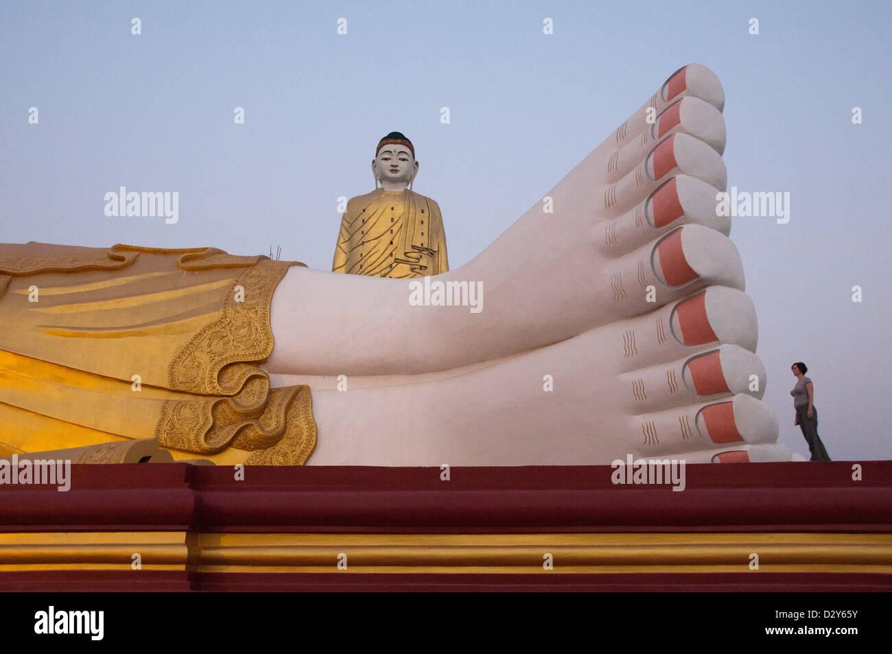 Füße von riesigen liegenden Buddha mit Bodhi Tataung, Giant Buddha hinter stehen. Monywa, Myanmar (Burma) Stockbild