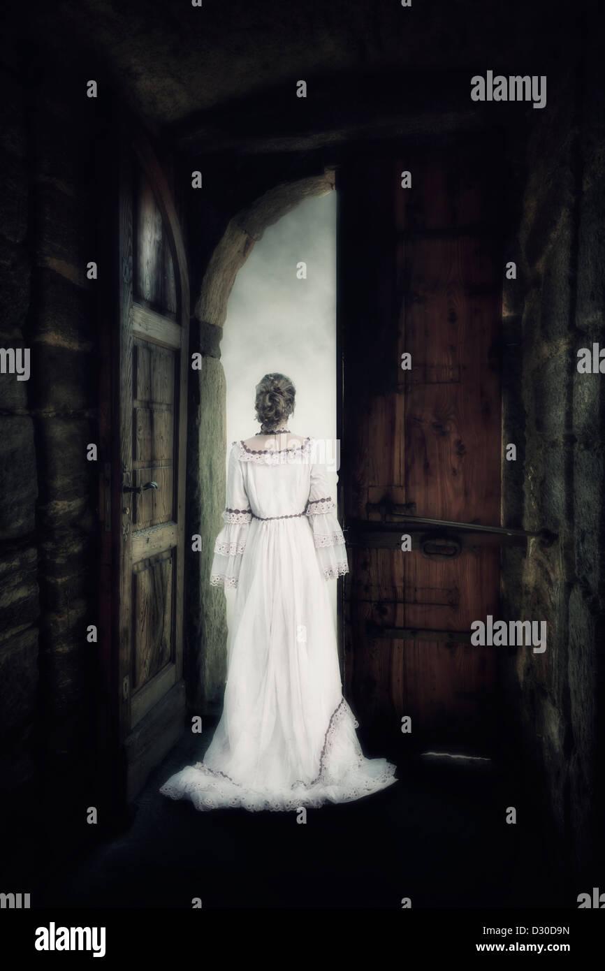 eine Frau in einem eleganten Kleid steht in das Tor eines alten Schlosses Stockbild