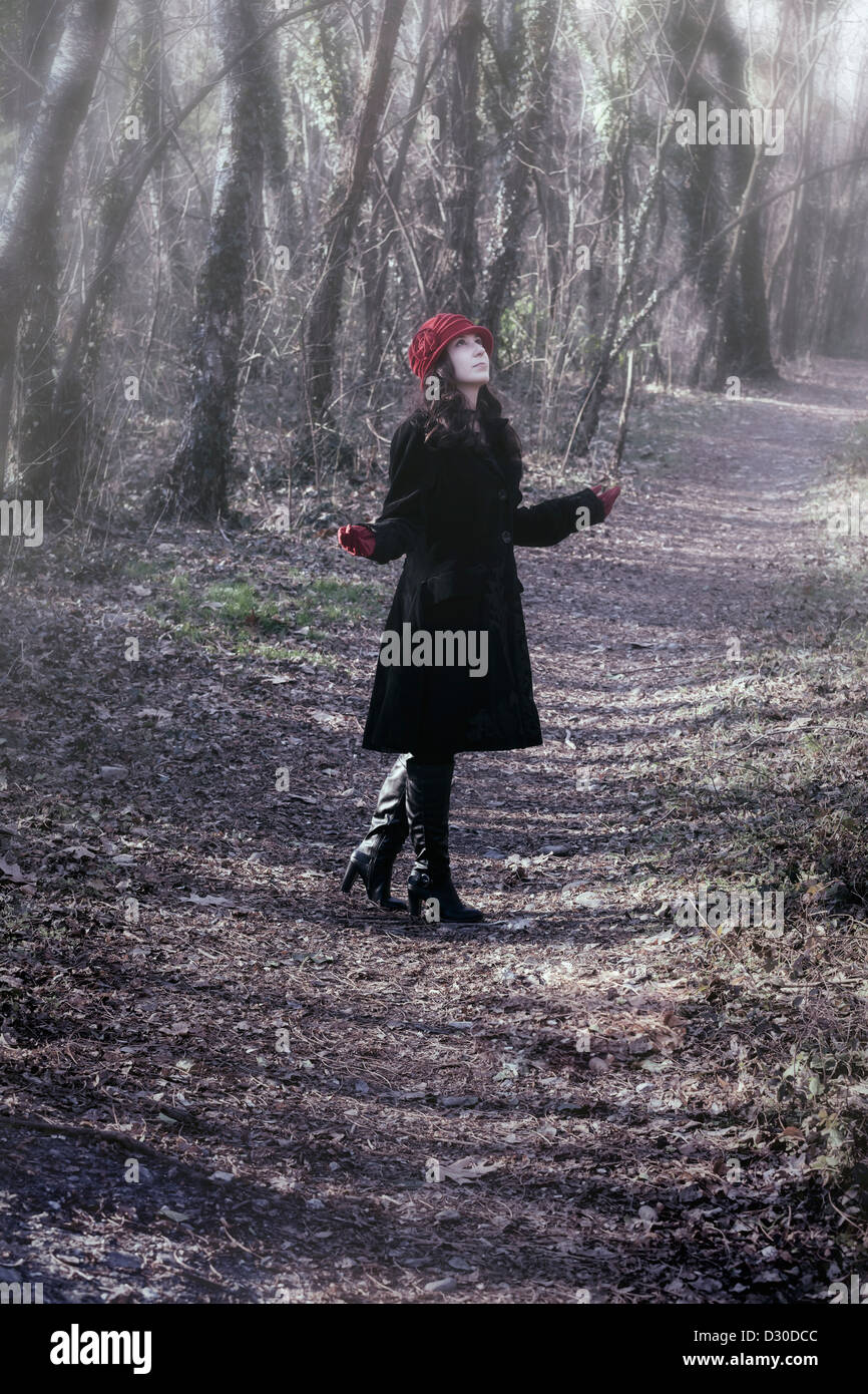 eine Frau in einem schwarzen Mantel mit roten Hut steht im Wald Stockbild