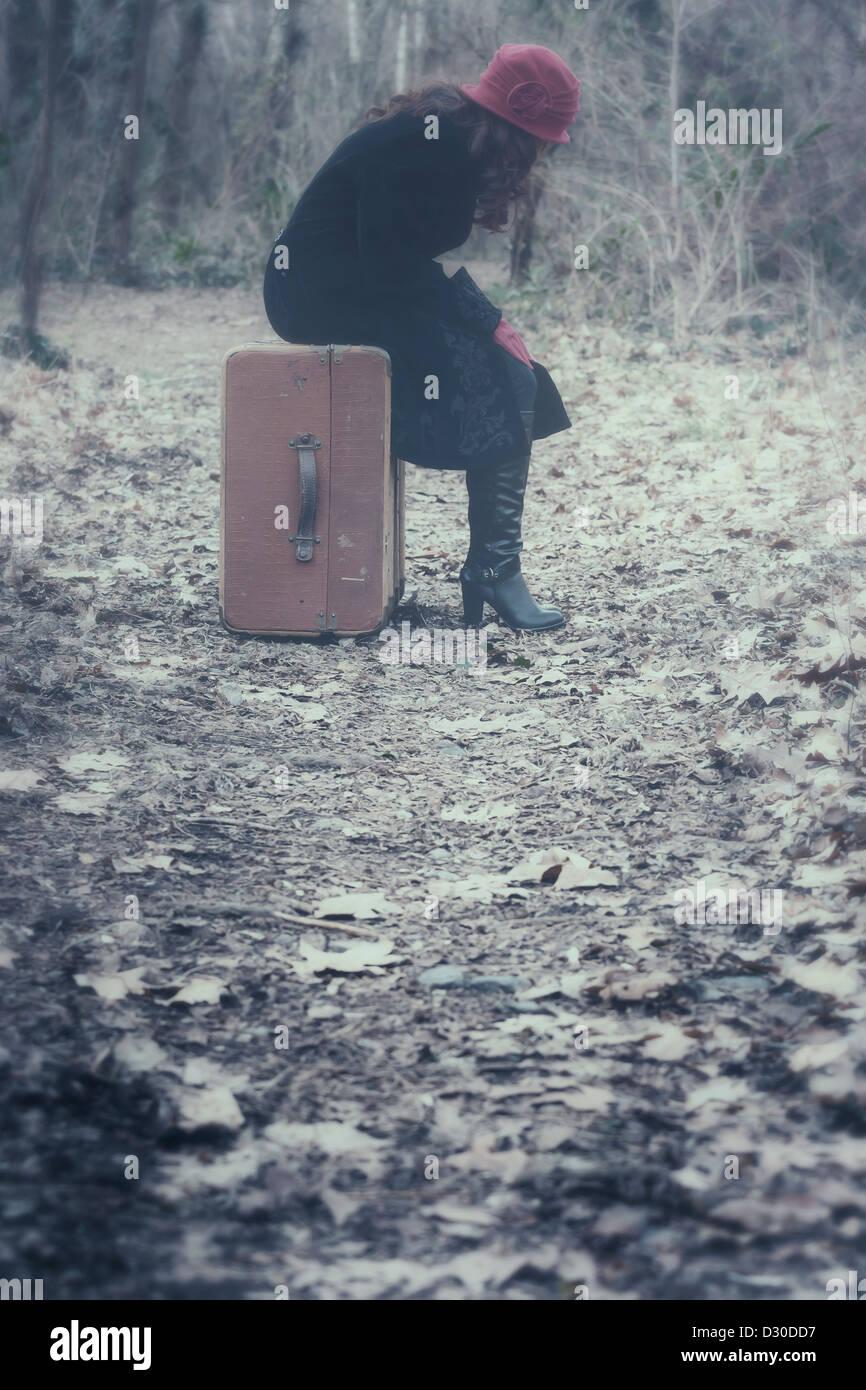 eine Frau mit einem schwarzen Mantel und eine rote Mütze sitzt auf einem alten Koffer im Wald Stockbild