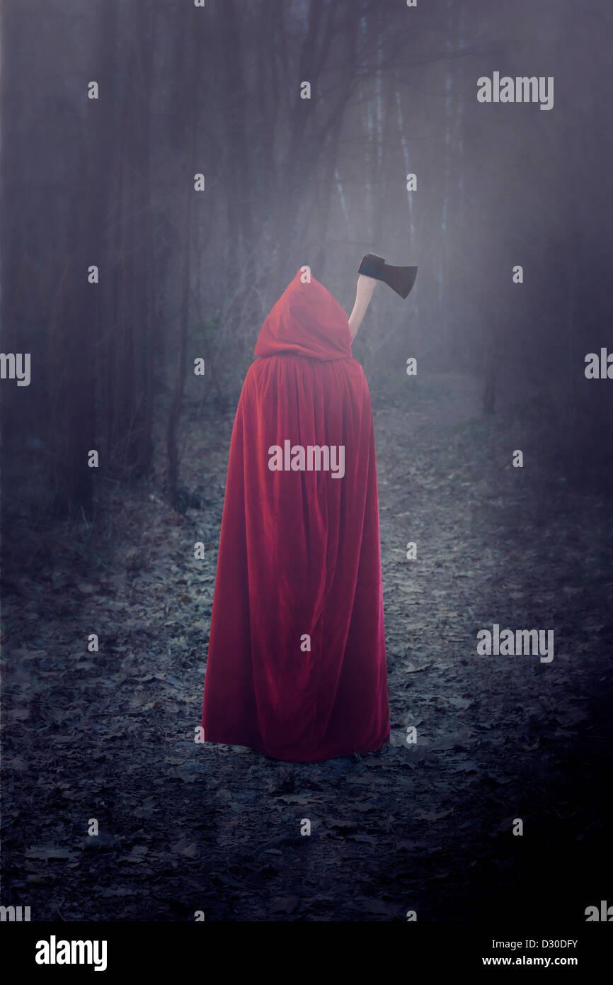 eine Frau in einem roten Mantel mit einer Axt Stockbild