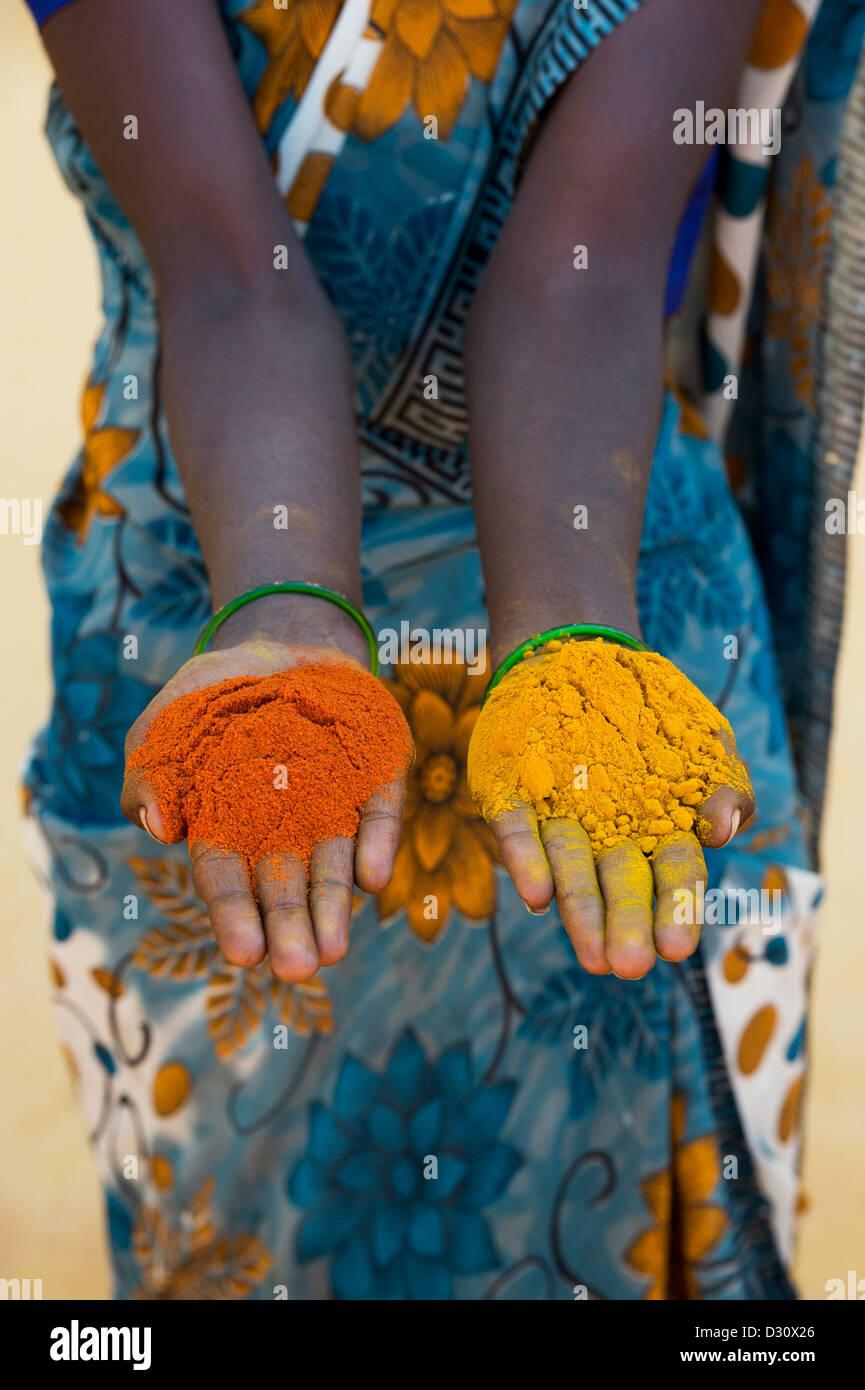 Indische Dorf Frau Kurkuma und Chili-Pulver in ihren Händen hält. Andhra Pradesh, Indien Stockbild