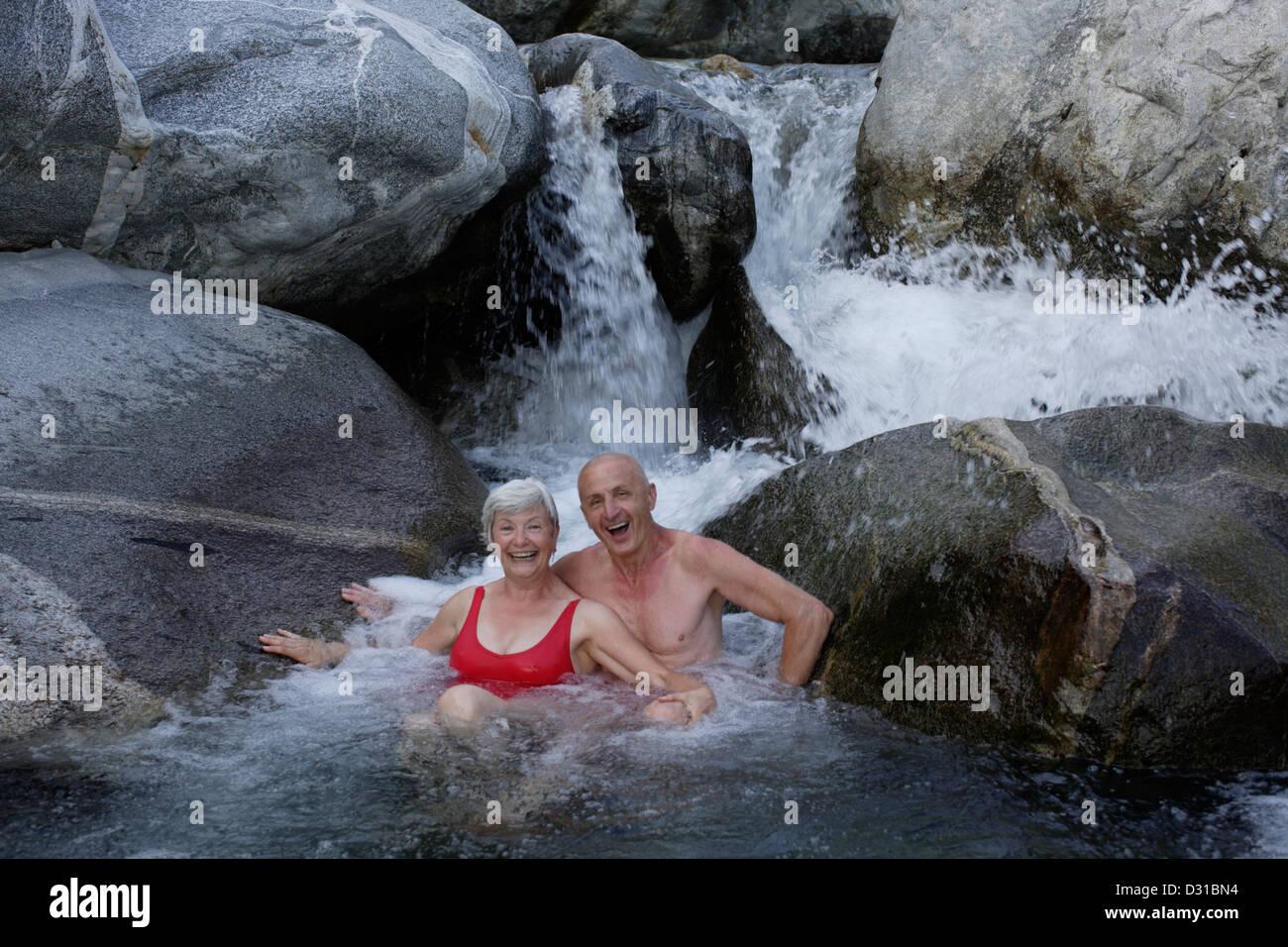 Senioren beim Baden im Bergfluss Stockbild