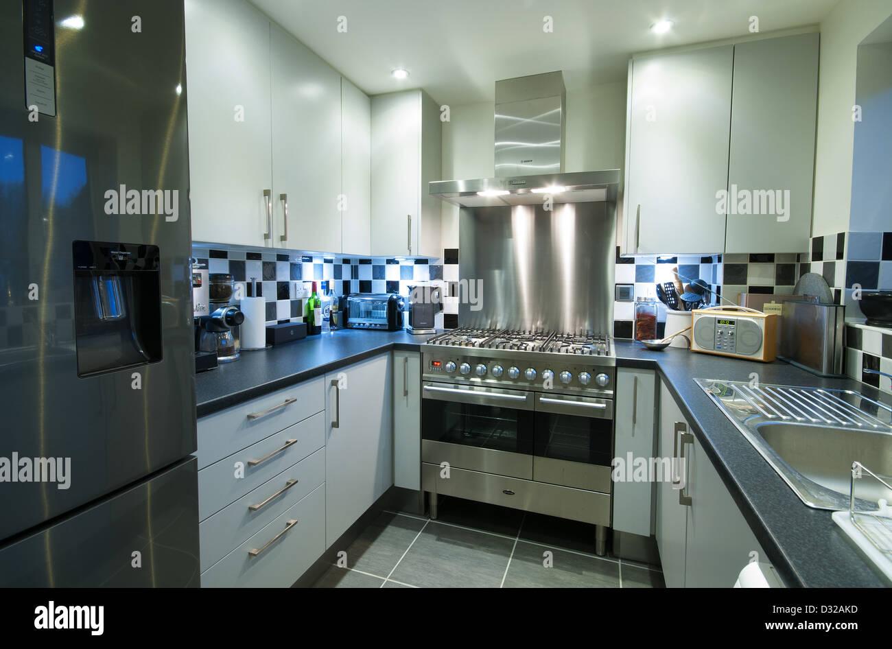 Eine kleine, moderne Küche mit einem Kühlschrank mit Gefrierfach ...