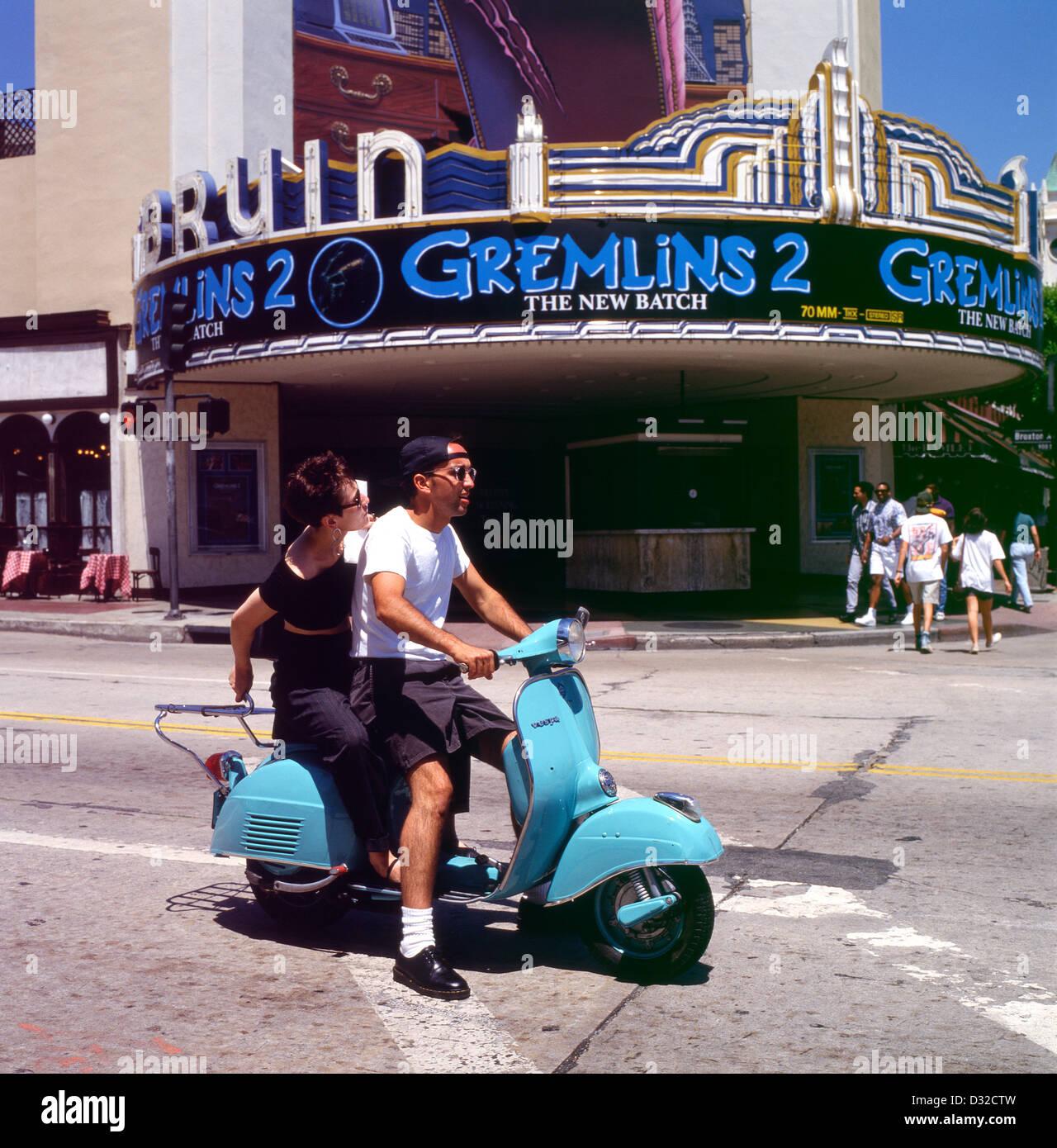 Paar auf einem Motorroller fahren vorbei an Gremlins 2 Film bei Bruin Westwood Theatre Los Angeles, Kalifornien Stockbild