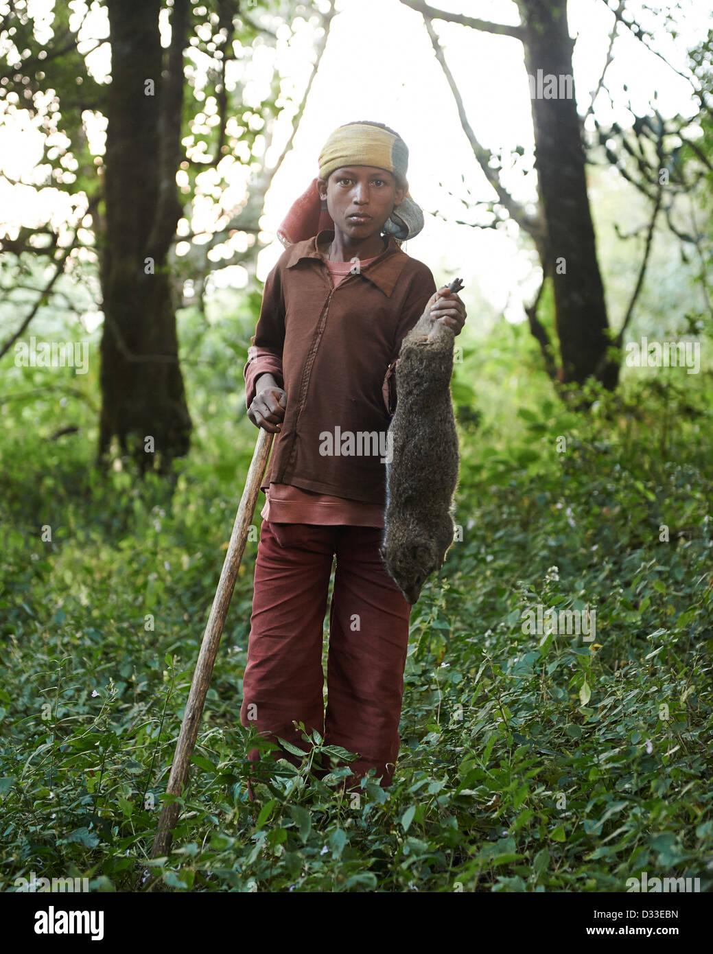 Ein kleiner Junge hält ein neu geschlachteten Ashkoko, ein Tier ähnlich dem eines Kaninchens Stockbild