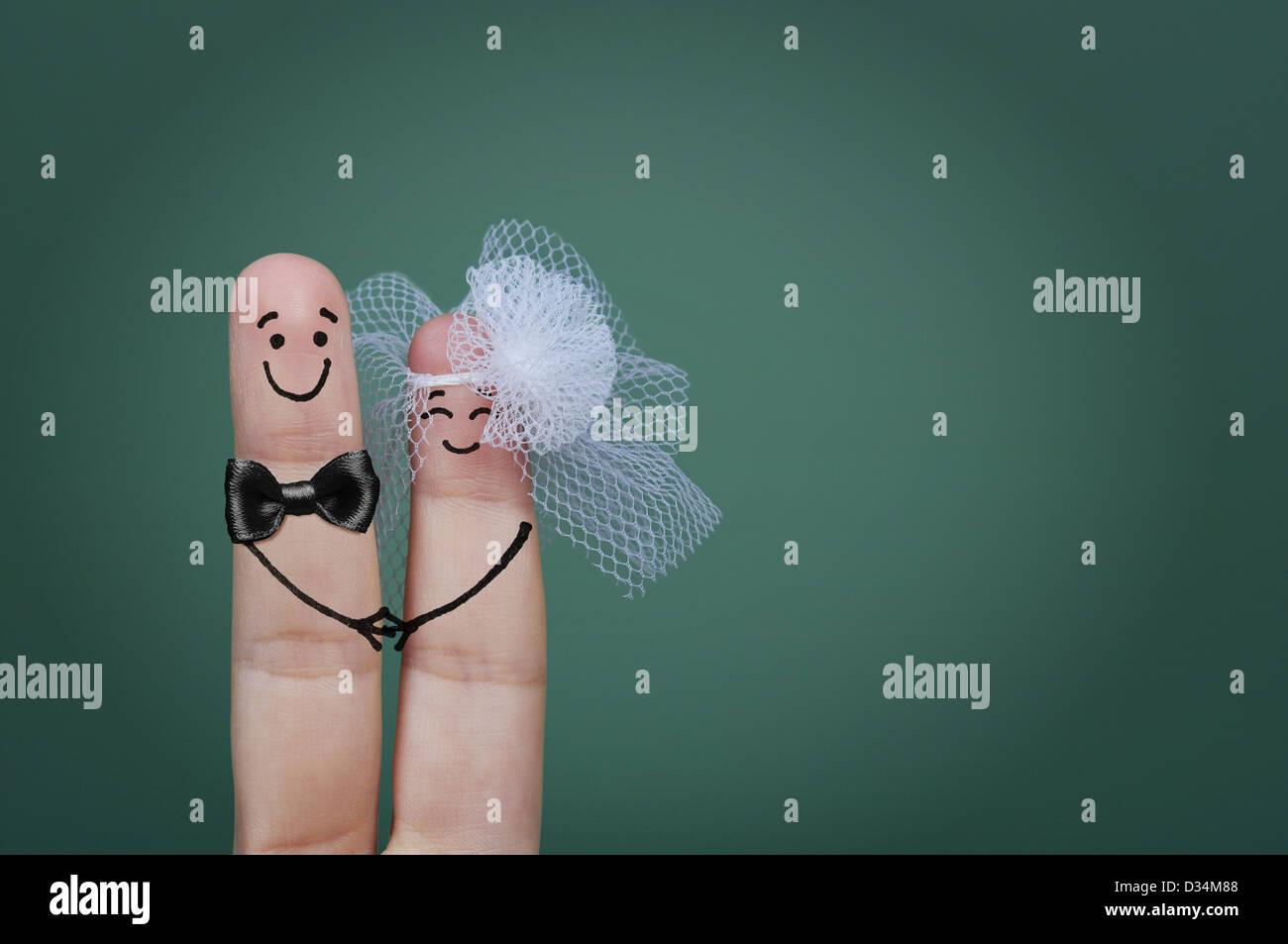 Zwei glückliche Finger als Braut und Bräutigam mit Schleier und Fliege verziert Stockfoto