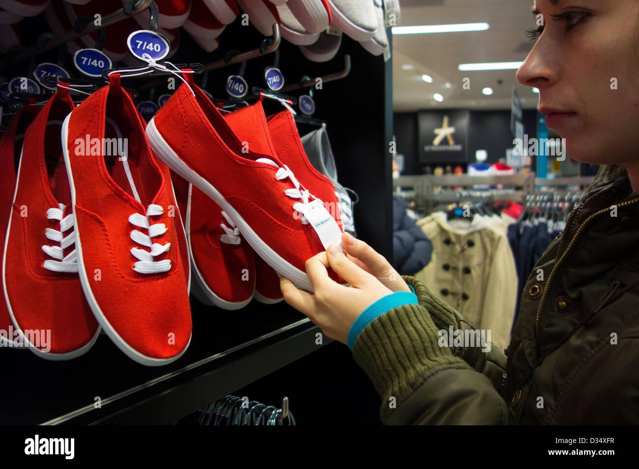 8f6e38cc45 Junge Frau, die roten Schuhe bei Primark betrachten Stockfoto, Bild ...