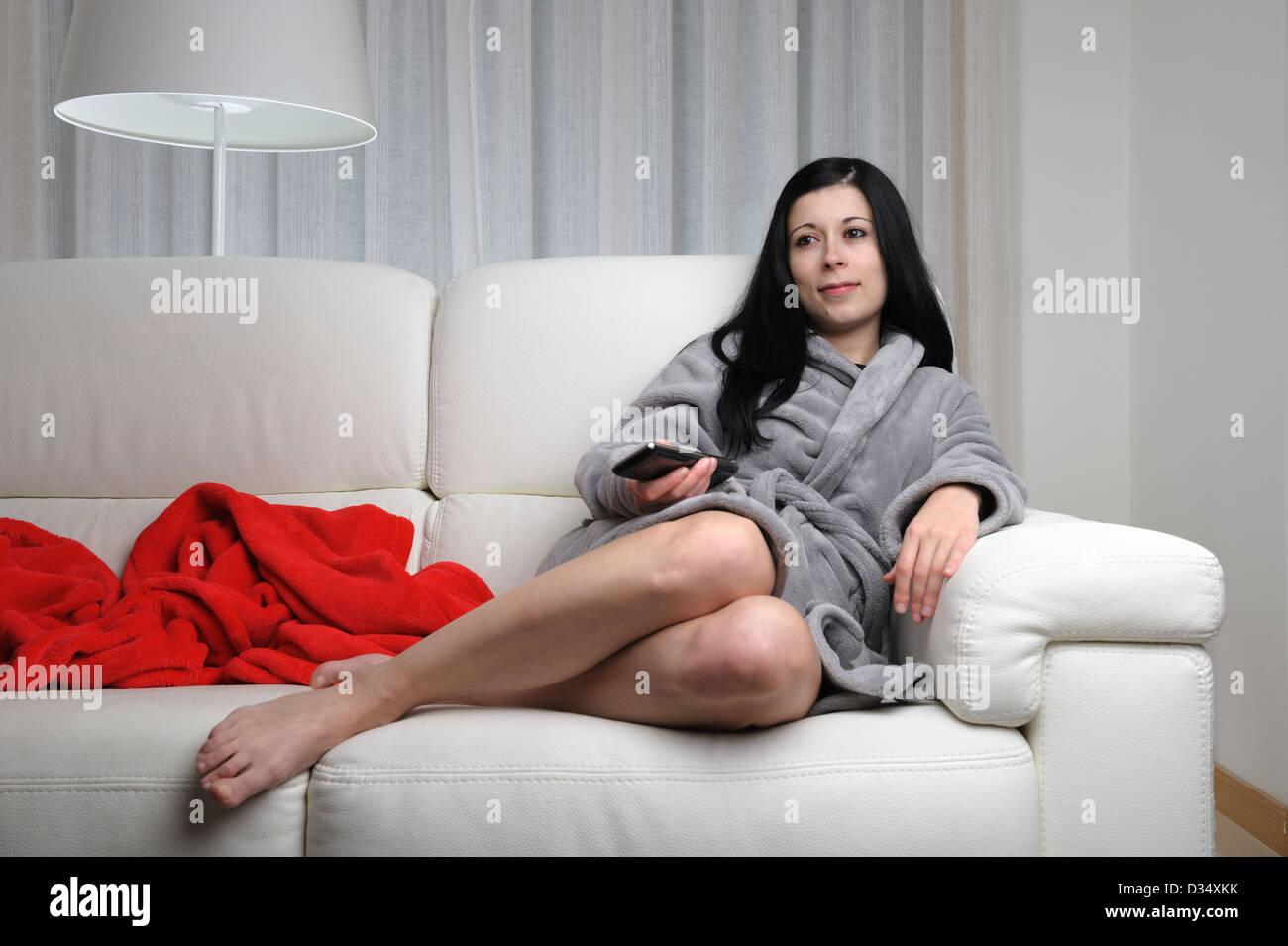 junge frau die zu hause vor dem fernseher sitzt auf einem. Black Bedroom Furniture Sets. Home Design Ideas