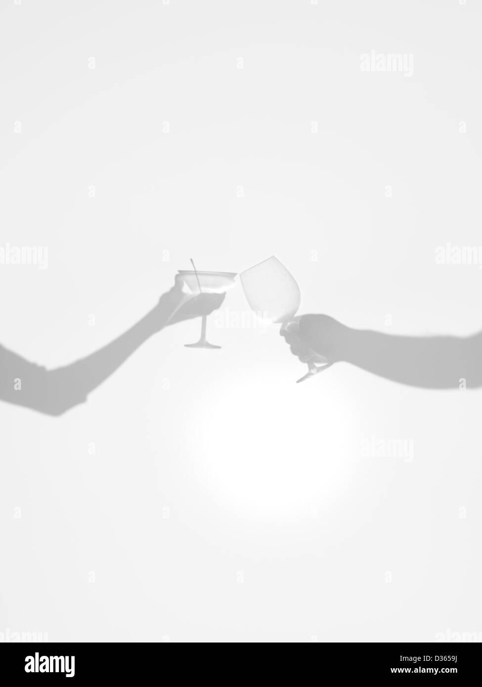 Nahaufnahme von zwei Händen Silhouetten halten zwei verschiedene Gläser, hinter eine diffuse Oberfläche jubelt Stockfoto