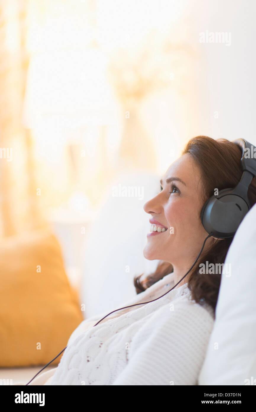 USA, New Jersey, Jersey City, Frau Musikhören zu Hause Stockbild