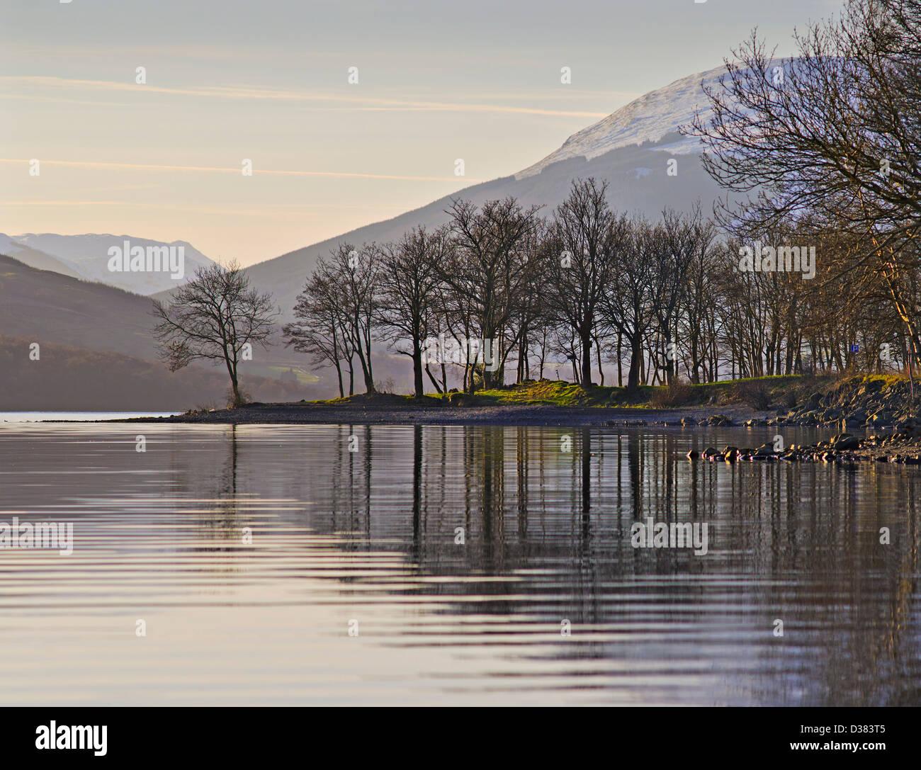 Loch Earn mit Silhouette Landzunge und Bäume mit entfernten Hügeln, Perthshire, Schottland Stockbild