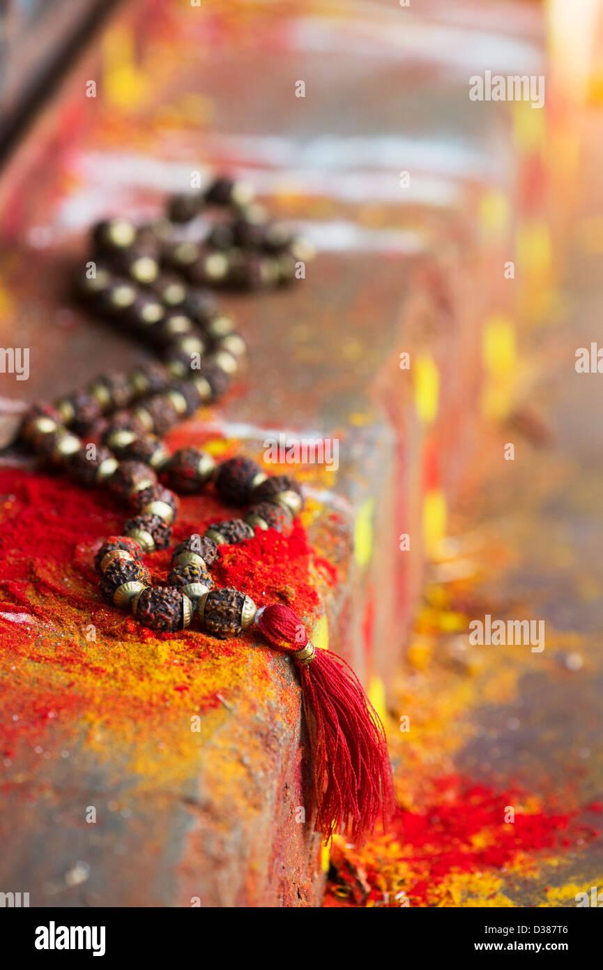 Indische Rudraksha / Japa Mala Gebetskette auf den Stufen des indischen Bauerndorf Schrein / Tempel. Andhra Pradesh, Indien. Selektiven Fokus. Stockfoto