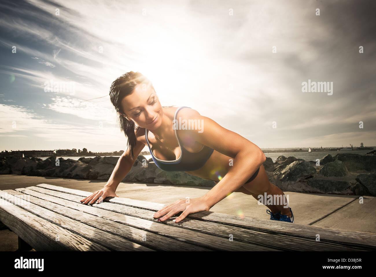 Frau tut Push ups auf Parkbank Stockbild