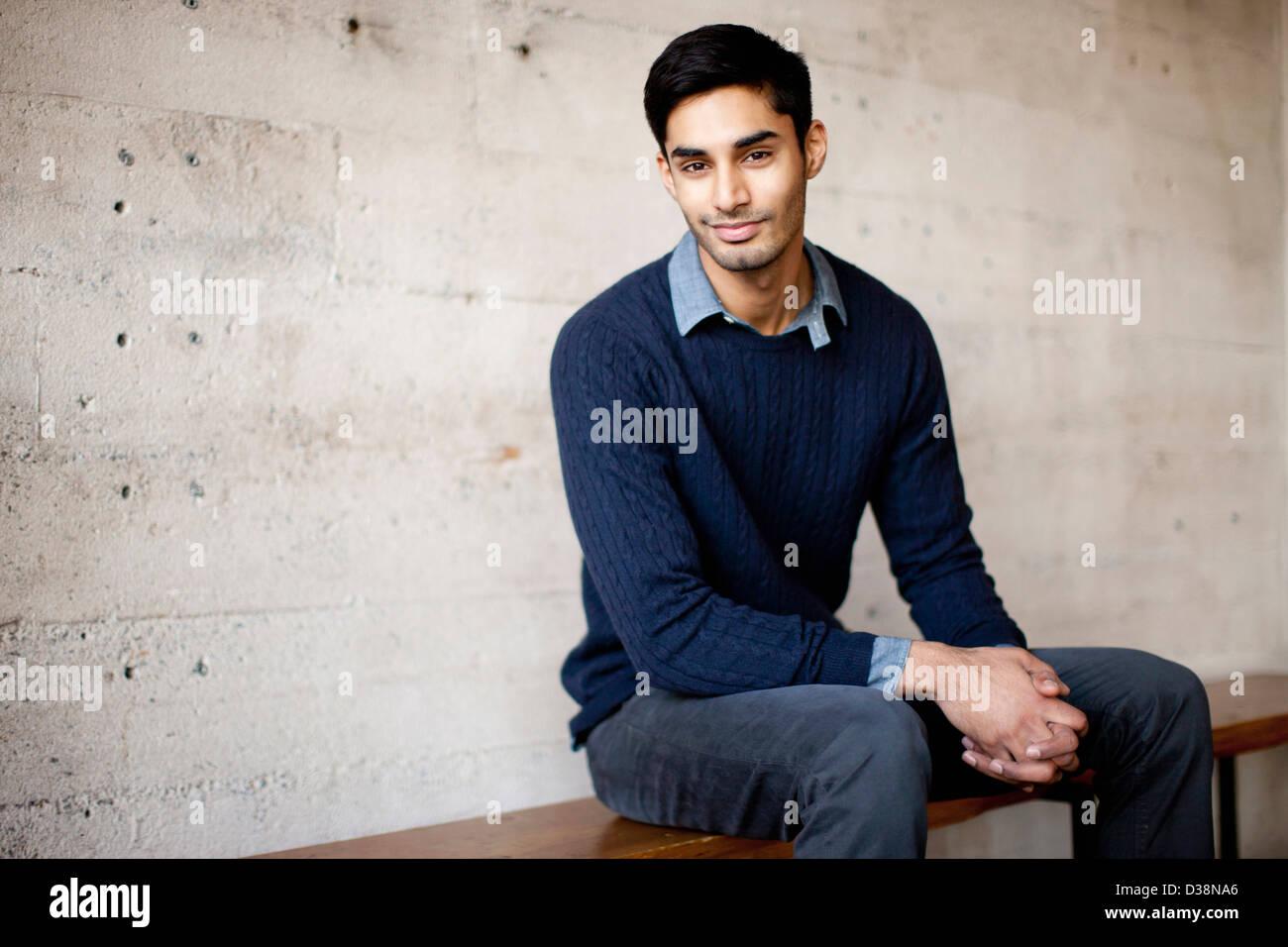 Lächelnder Mann auf Bank sitzend Stockbild