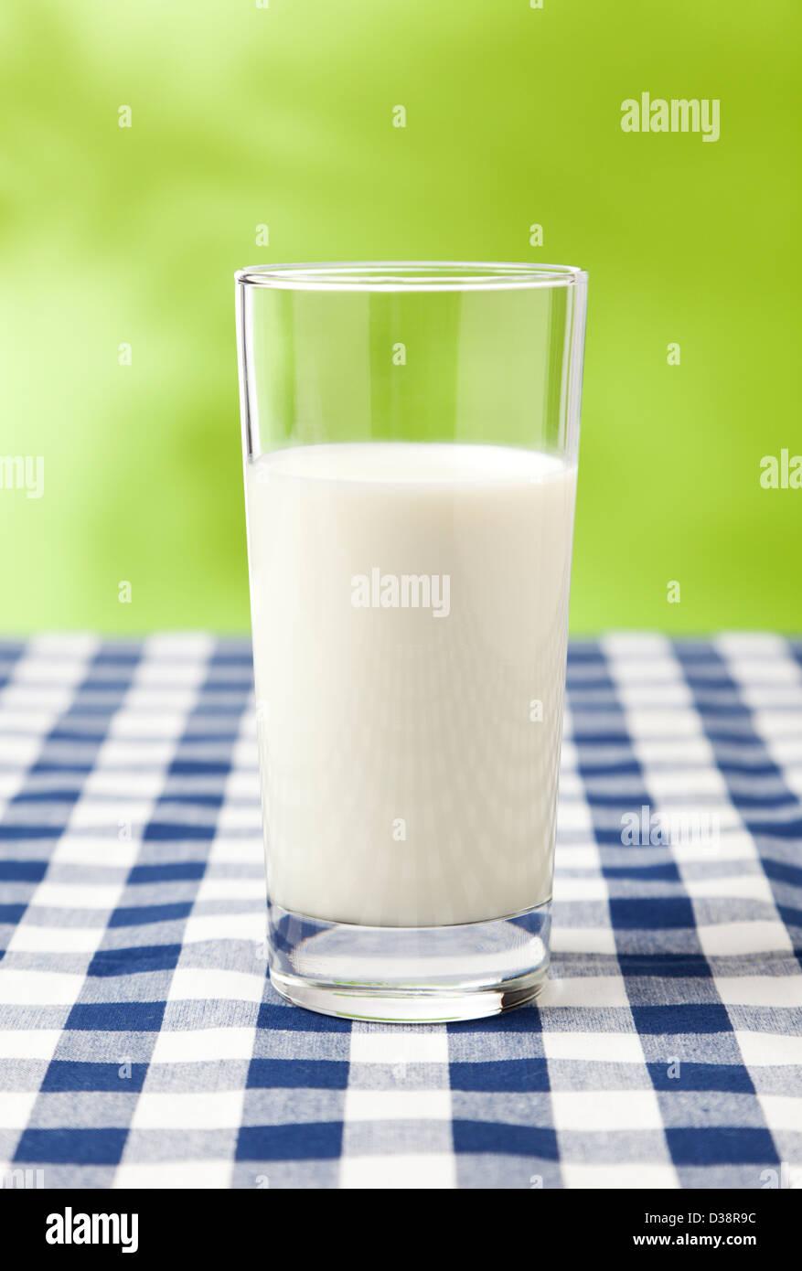 Glas Milch auf karierten Tisch Tuch, grüner Hintergrund Stockbild