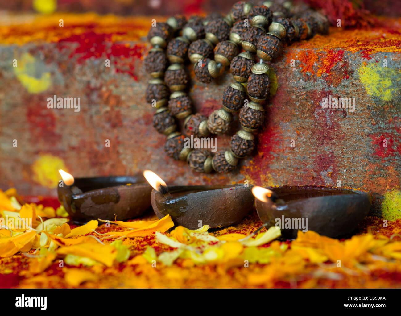 Öl-Lampen und indischen Rudraksha / Japa Mala Gebetskette auf den Stufen des indischen Bauerndorf Schrein / Tempel. Indien Stockfoto