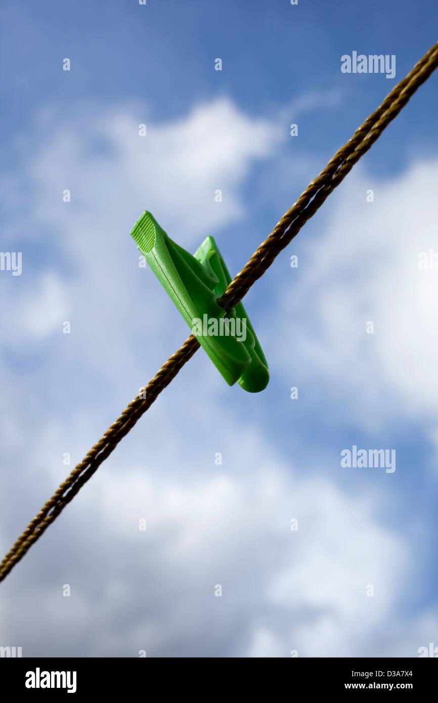 Einem einzigen grünen Wäscheklammer oder Pin an einer Wäscheleine vor einem bewölkten blauen Stockbild