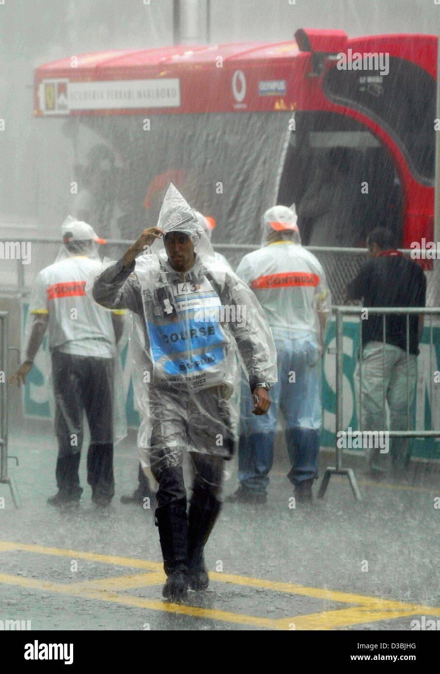 (Dpa) - im strömenden Regen ein Helfer in einem Regenmantel Spaziergänge durch die Boxengasse auf die Stockbild