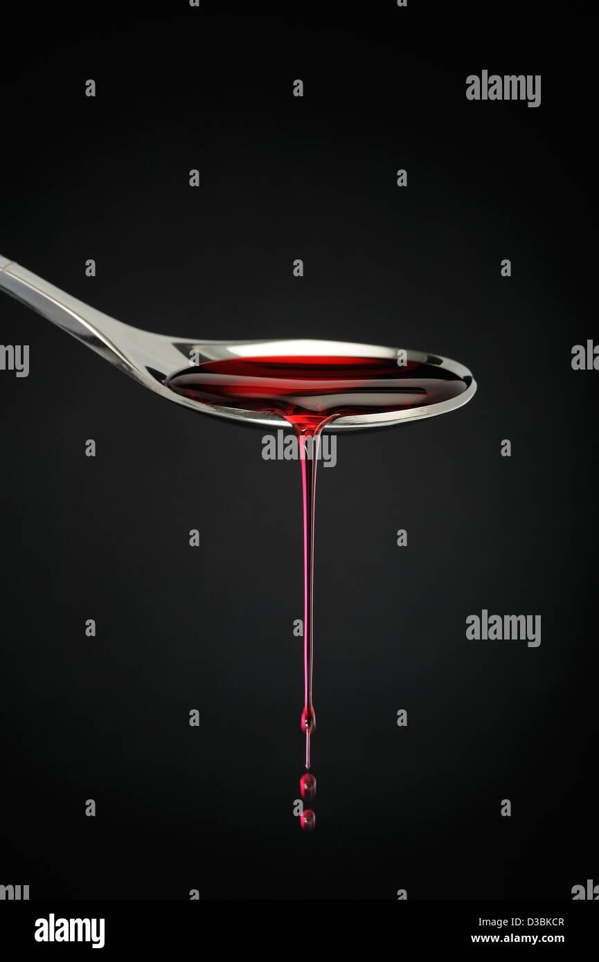 Teelöffel mit roten Flüssigkeit in schwarz schwarz-Boden tropft. Stockbild