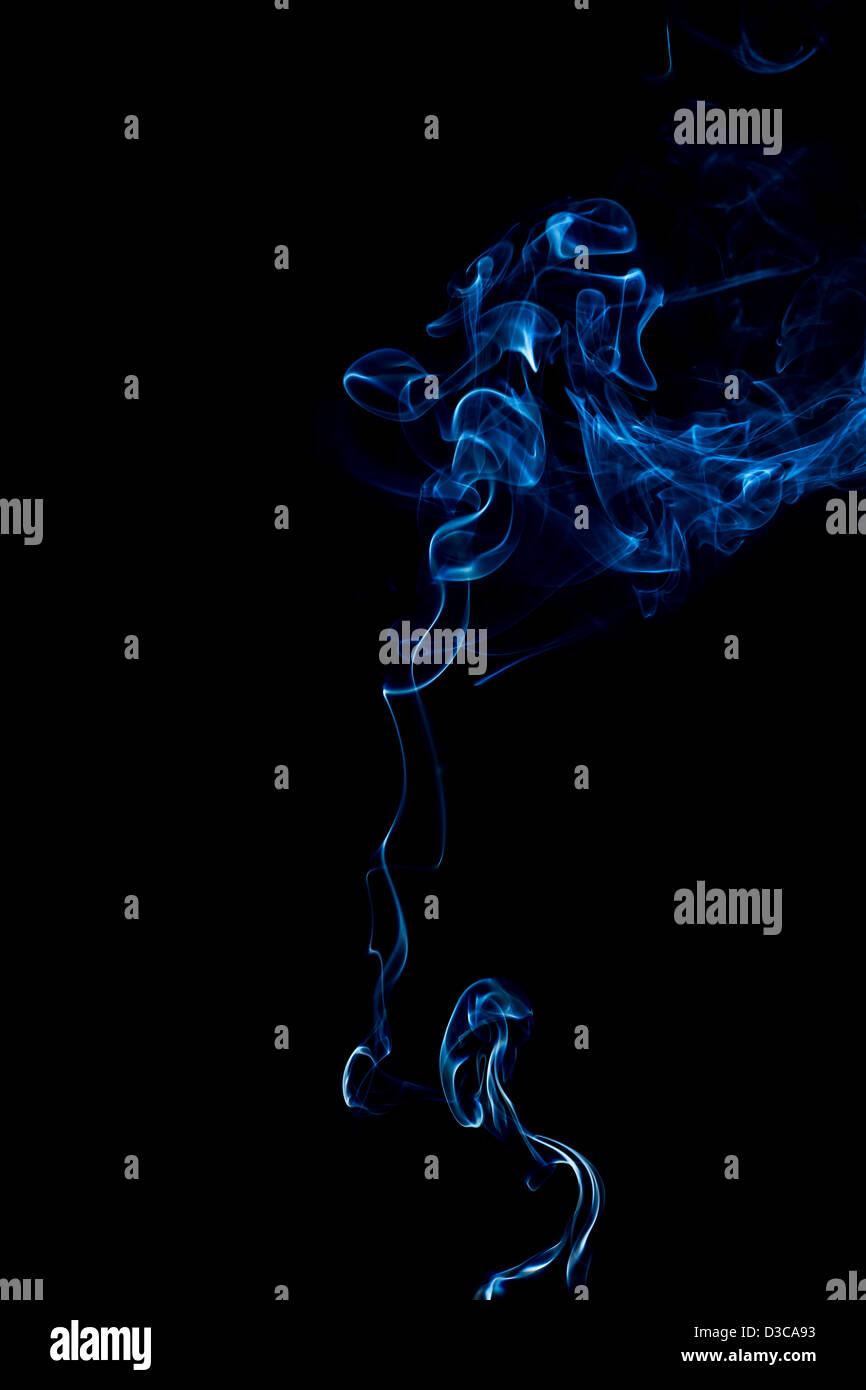 blaue Ringe und locken von Rauch auf schwarzem Hintergrund Stockbild