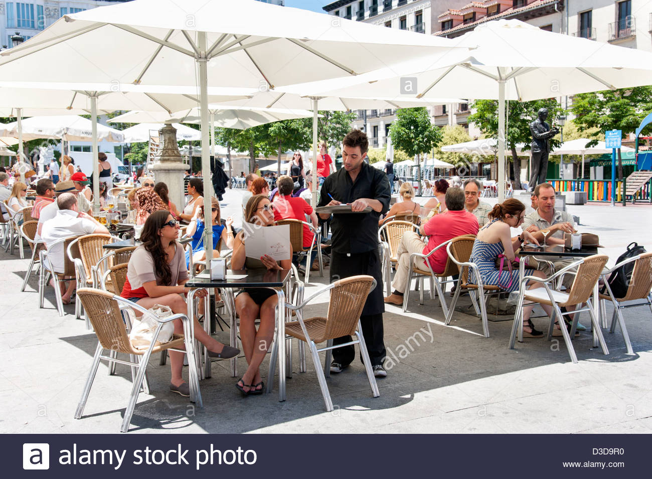 Menschen, die Bestellung von Getränken auf Stehtische auf Plaza de Santa Ana, Barrio de Las Letras, Madrid, Stockbild