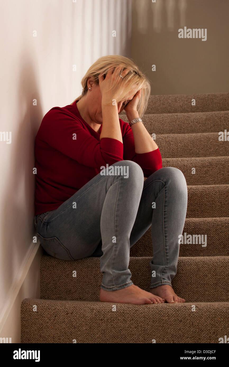 Kopf der Frau in Händen allein sitzen. Modell und Besitz (Fotograf) veröffentlicht. Stockbild
