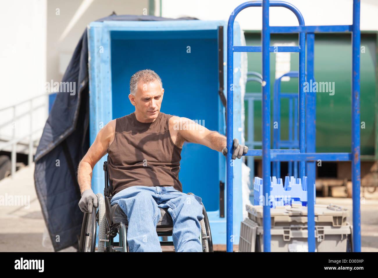 Laden Hafenarbeiter mit Querschnittslähmung im Rollstuhl bewegen einen Hand-LKW Stockfoto