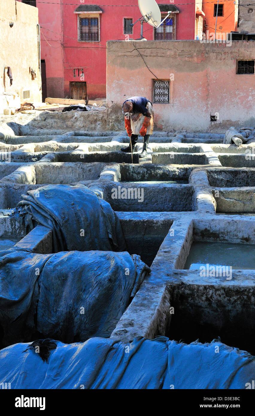Mann oben auf die Gerbereien Verarbeitung Bottiche, tendenziell die Kuh Häute in der Gerbereien in Marrakesch Stockbild