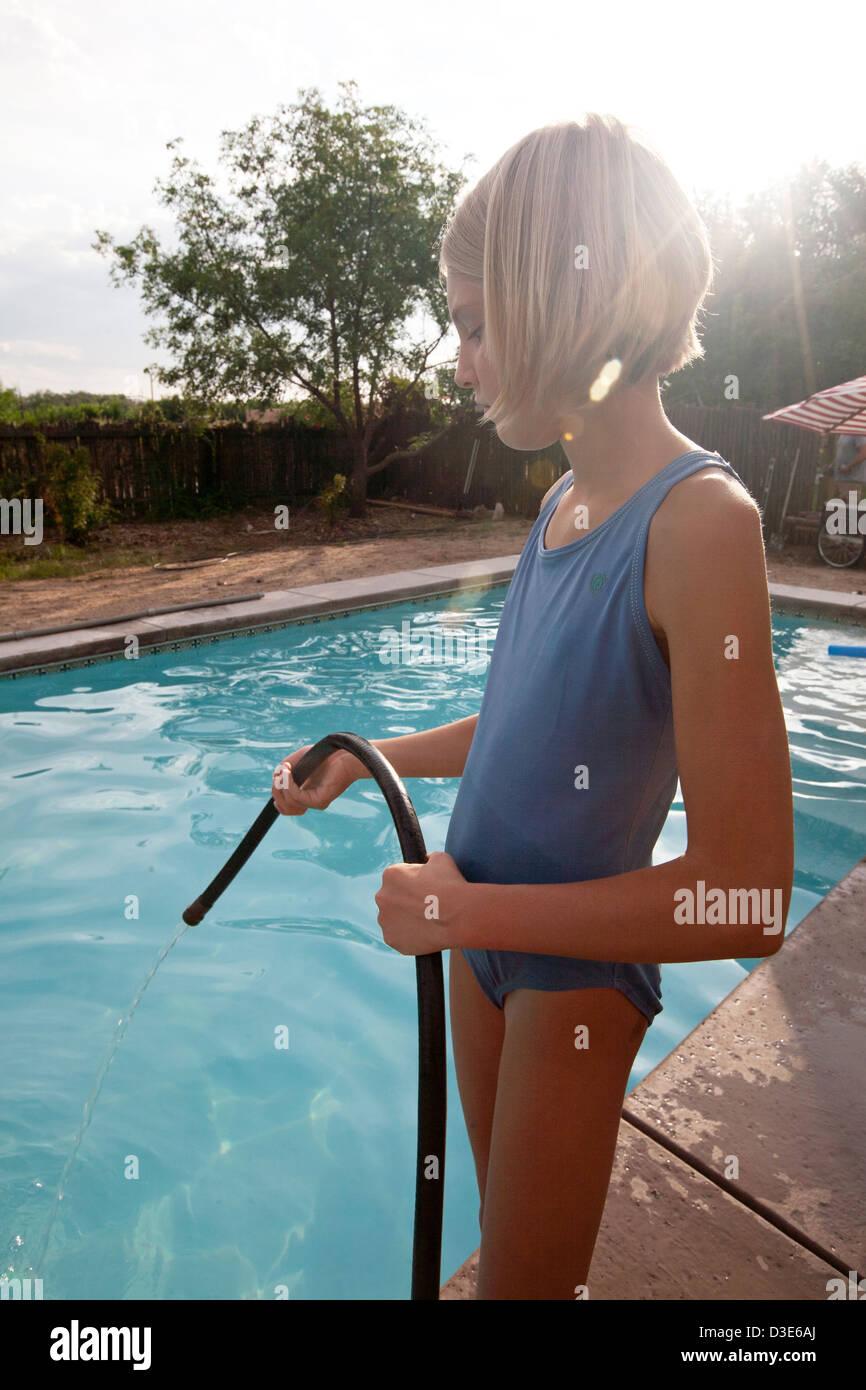 Zehn Jahre altes Mädchen gießt Wasser in ein Schwimmbecken aus einem Schlauch. Stockfoto