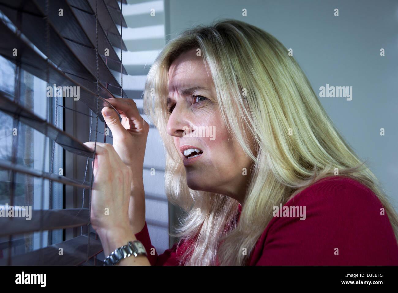 Profil einer verängstigten blonde Frau durch eine hölzerne Fensterjalousie. Stockbild