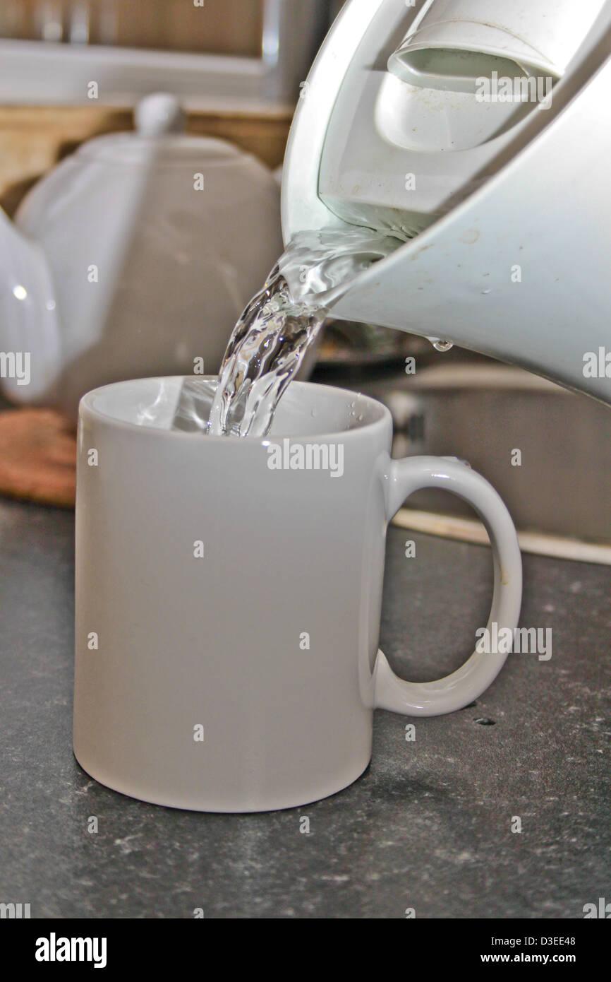 kochendes Wasser wird aus einem Kessel in eine weiße Tasse gegossen ...
