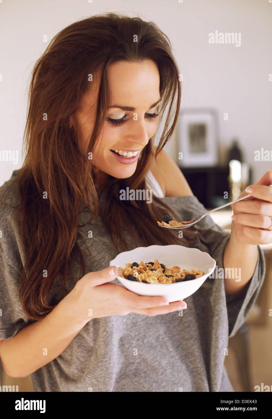 Lächelnde Frau genießen ihre Schüssel Müsli am Morgen Stockbild