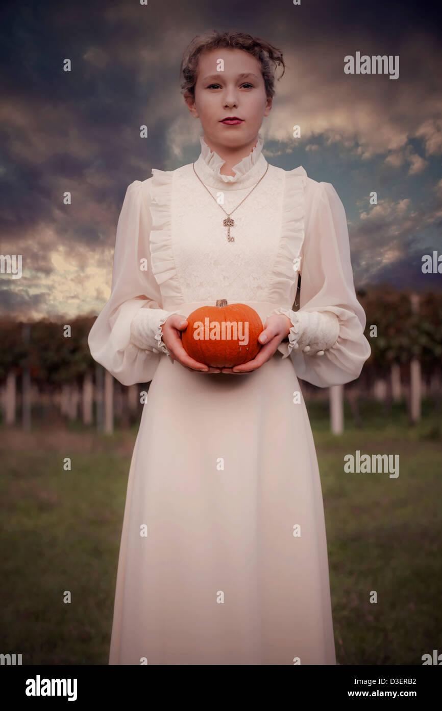 eine Frau in einem viktorianischen Kleid hält einen Kürbis Stockfoto
