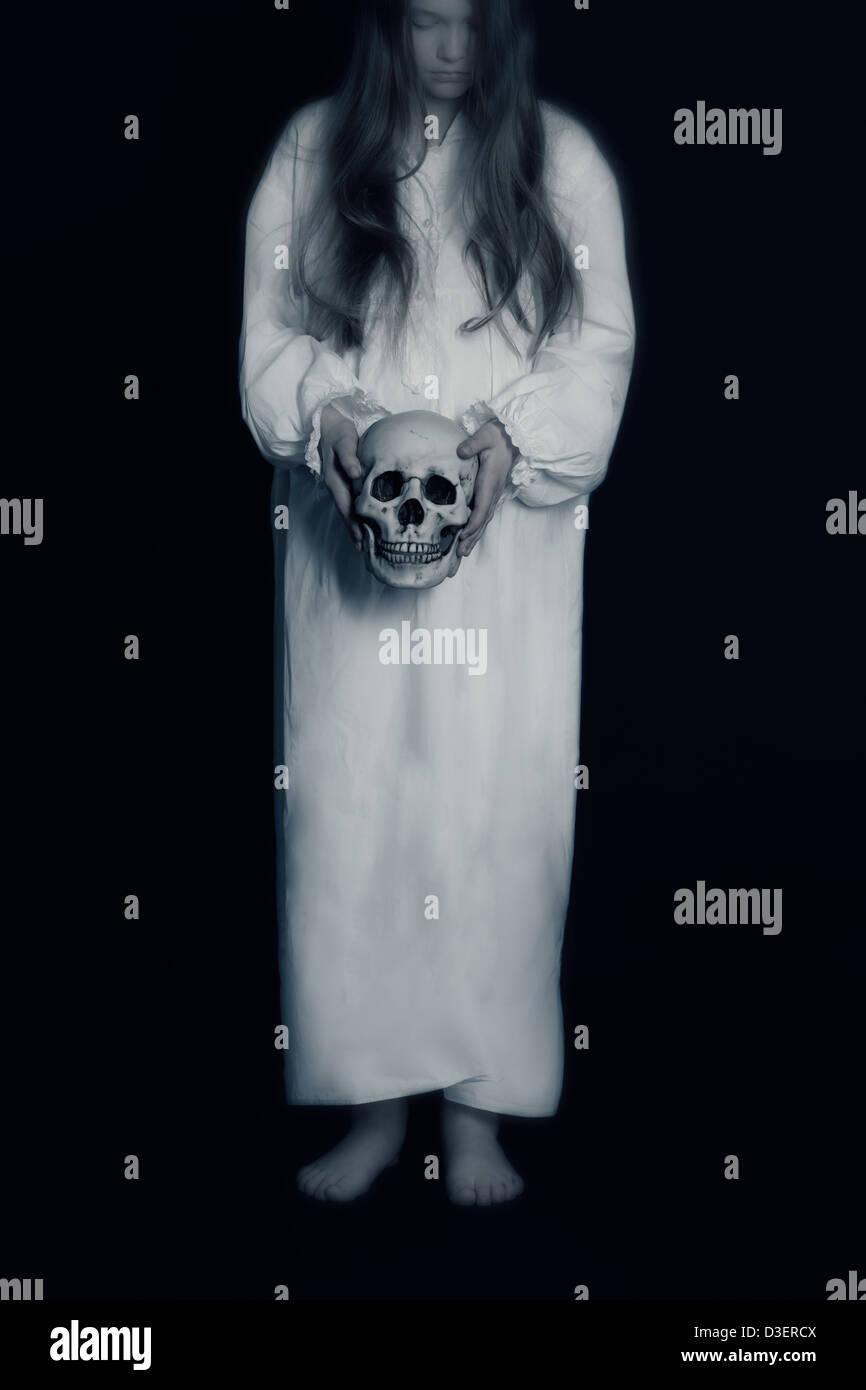 eine Mädchen in einem weißen Vintage-Kleid mit einem Totenkopf Stockbild