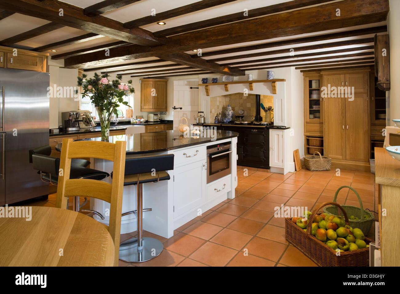 UK. Eine moderne Küche mit einer Kochinsel, AGA-Herd und Holzbalken ...