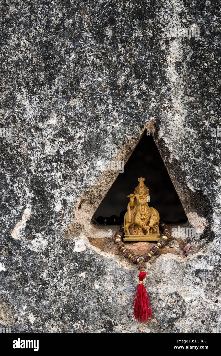 Lord Krishna Statue und indischen Rudraksha / Japa Mala Gebet Perlen in einer Tempelwand. Andhra Pradesh, Indien Stockfoto