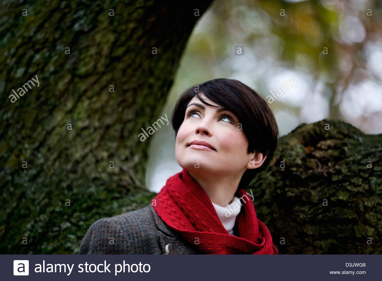 Eine Frau stand neben einem Baum im Herbst, Blick nach oben Stockbild