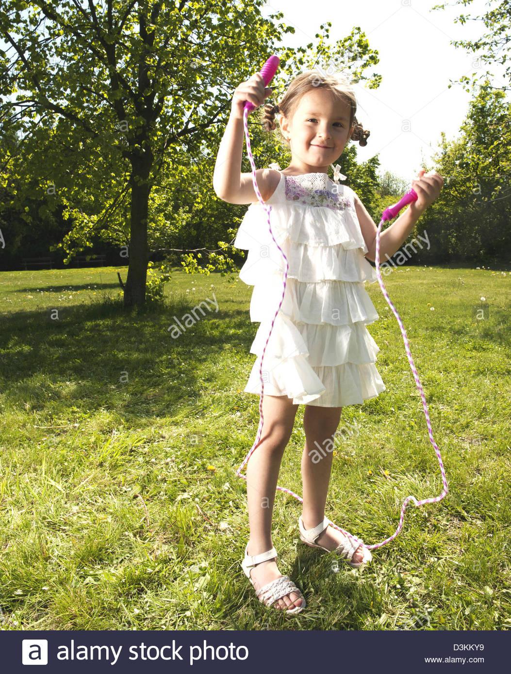 Kleine Mädchen spielen mit einem Springseil Stockbild