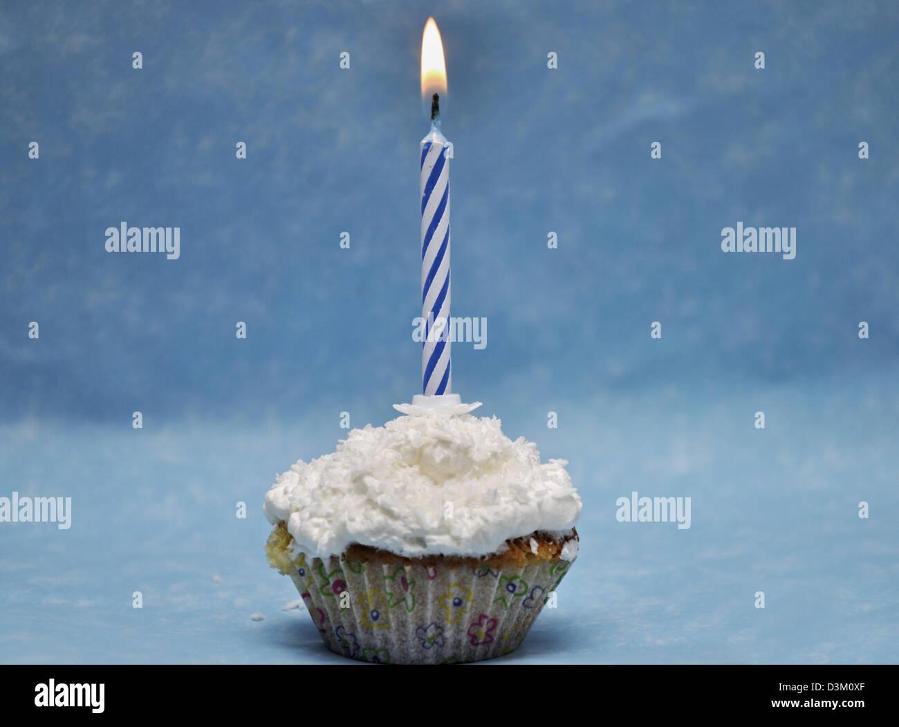 Vanille Cupcake mit brennende Kerze an der Spitze Stockbild