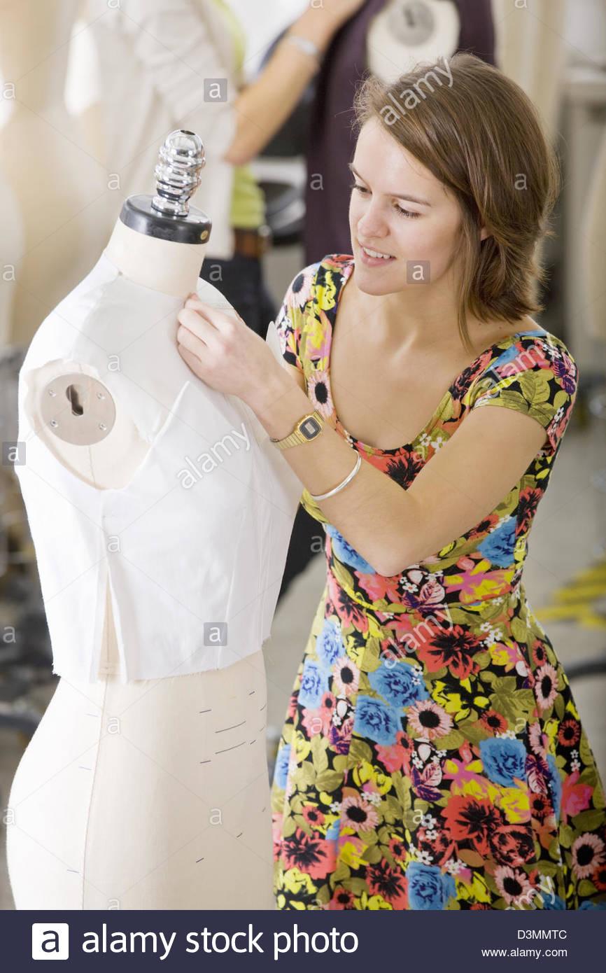 Mode-Design-Student arbeitet an Kleidungsstück an Puppe Stockbild