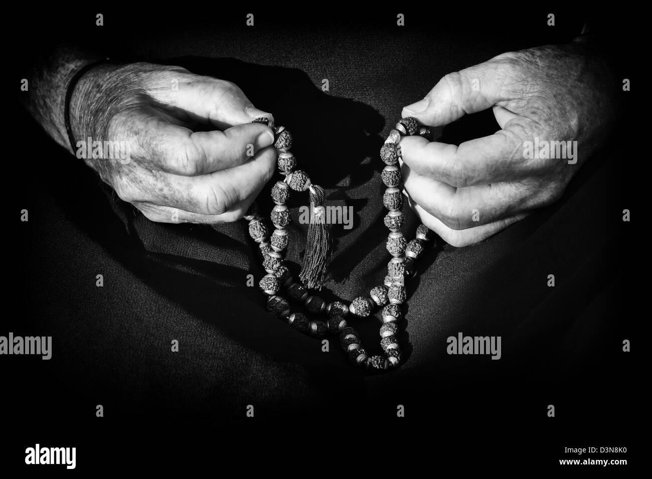 Old mans Händen mit indischen Rudraksha / Japa Mala Gebetskette. Monochrom Stockfoto