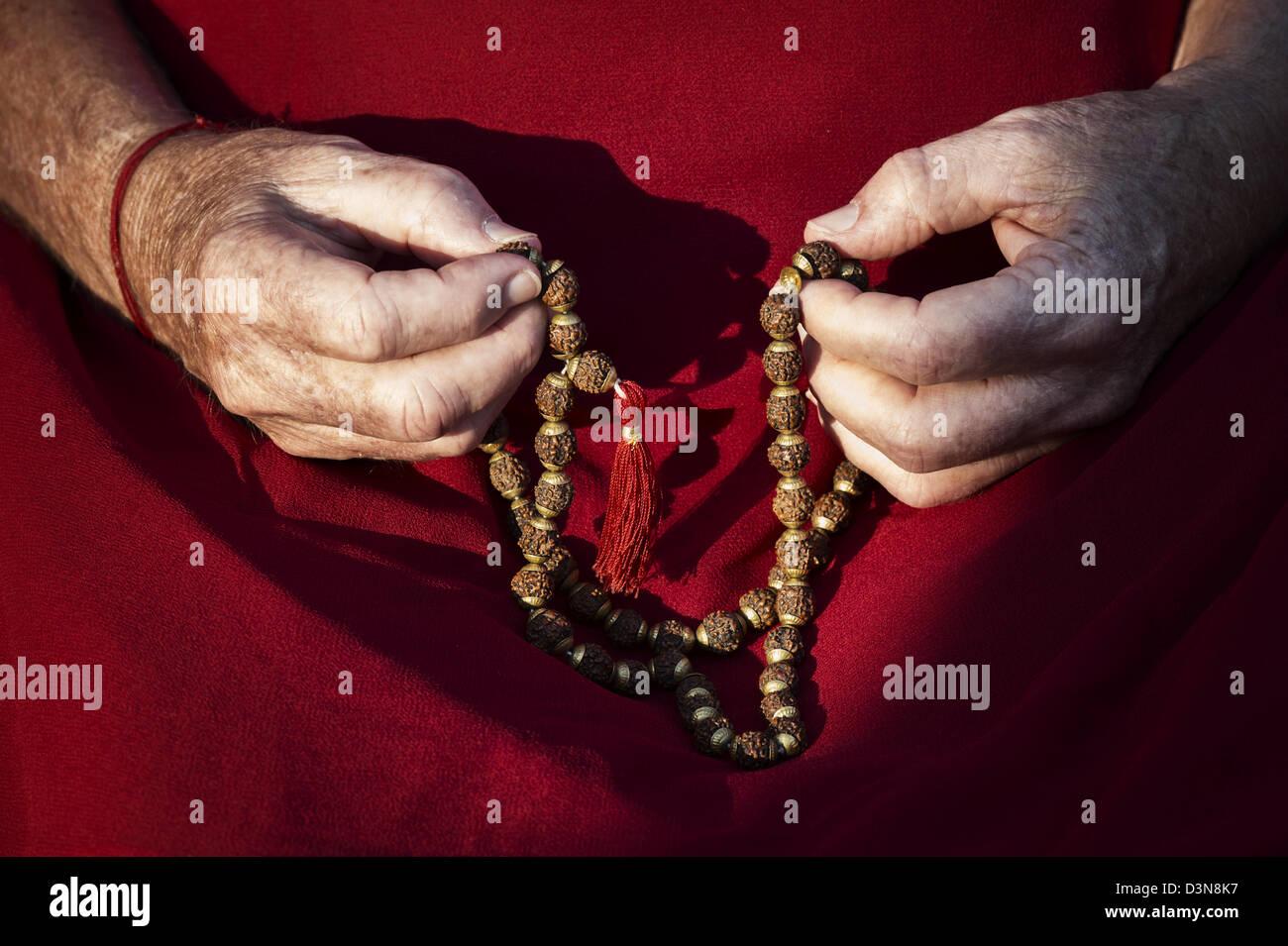 Old mans Händen mit indischen Rudraksha / Japa Mala Gebetskette Stockfoto