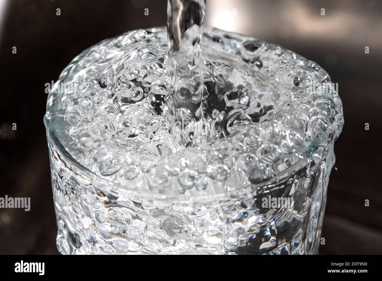 Wasser läuft in einem Glas, aus einem Wasserhahn in der Küche ...