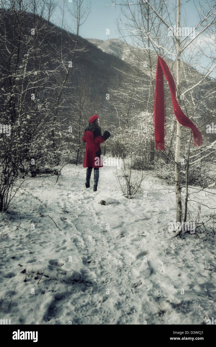 eine junge Frau in einem roten Mantel läuft durch den winterlichen Wald und verlor ihren roten Schal Stockbild