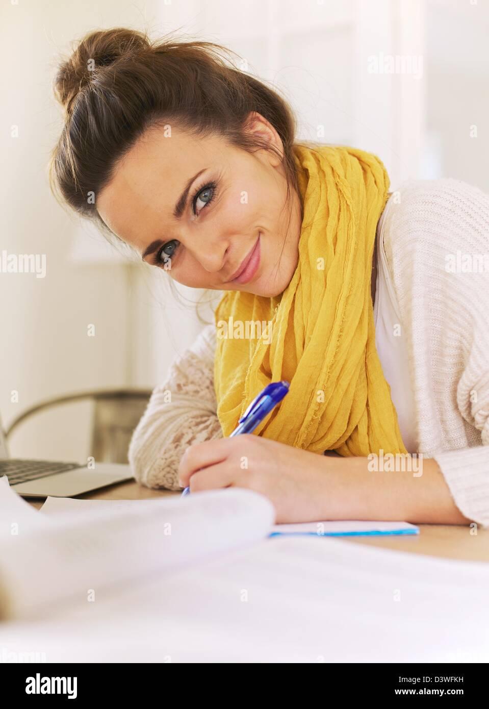 Nahaufnahme einer schönen lächelnden Frau Blick in die Kamera während des Schreibens auf ihrem Merkzettel Stockbild
