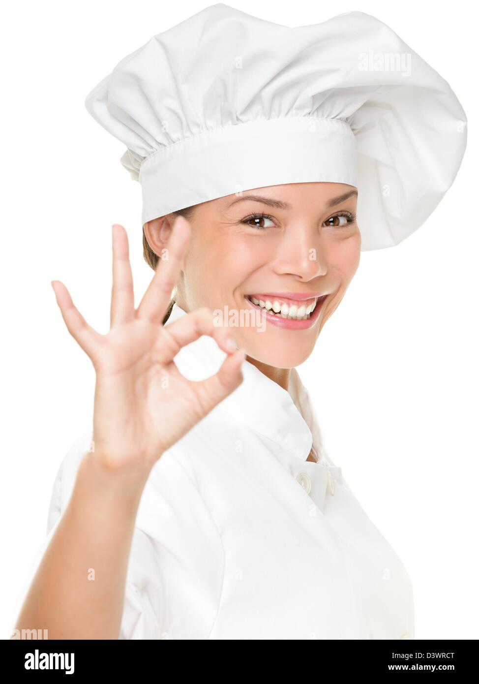 Porträt von Mischlinge weiblich Kochen tragen Kochmütze zeigt OK Handzeichen für Perfektion isoliert Stockbild