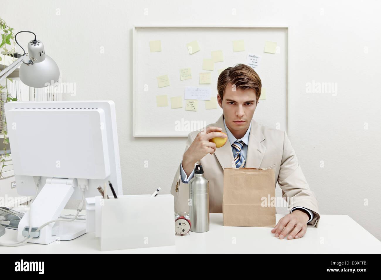 Ein Konzept-Foto von eine junge Büroangestellte versucht, Geld zu sparen, indem man Mittagessen zu arbeiten. Stockbild